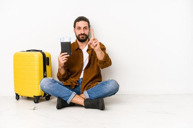 Giovane uomo caucasico seduto in possesso di un passaporto e una valigia isolata che mostra il numero uno con il dito.