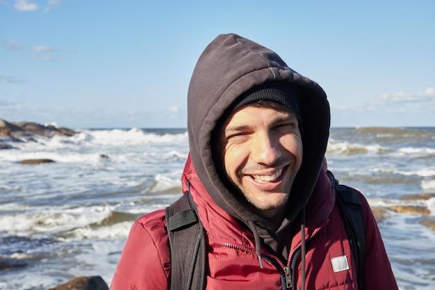 Giovane uomo caucasico che sorride alla macchina fotografica sulla spiaggia in inverno. indossa giacca e cappuccio.