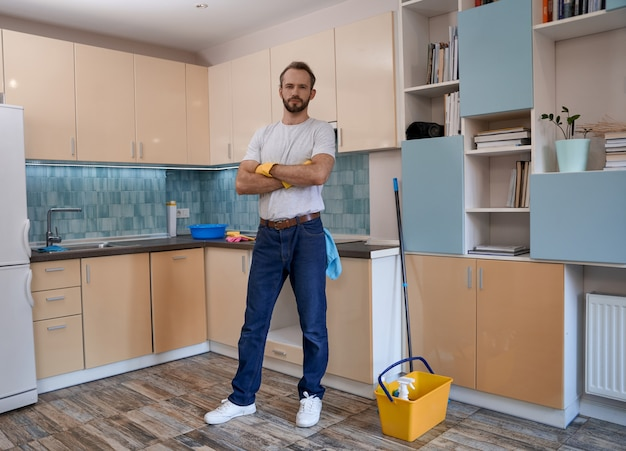 Giovane uomo caucasico in piedi con le mani incrociate in cucina