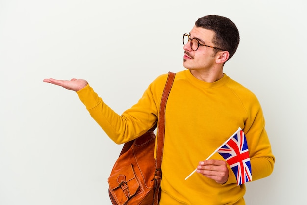 Giovane uomo caucasico che studia inglese isolato su sfondo bianco che mostra uno spazio di copia su un palmo e tenendo un'altra mano sulla vita.