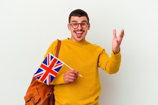 Giovane uomo caucasico che studia inglese isolato su bianco ricevendo una piacevole sorpresa, eccitato e alzando le mani.