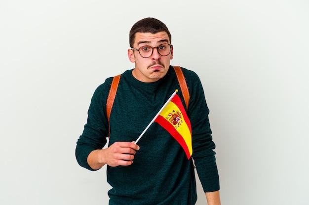 Giovane uomo caucasico che studia inglese isolato su bianco alza le spalle e apre gli occhi confusi.