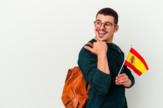 Giovane uomo caucasico che studia inglese isolato su punti di muro bianco con il pollice lontano, ridendo e spensierato