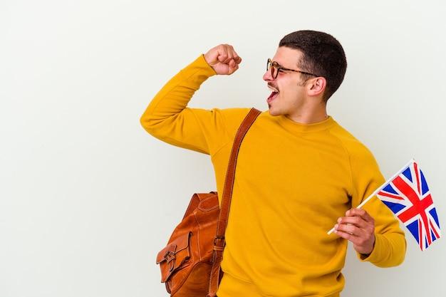 Giovane uomo caucasico che studia inglese isolato sul muro bianco alzando il pugno dopo una vittoria, concetto di vincitore.