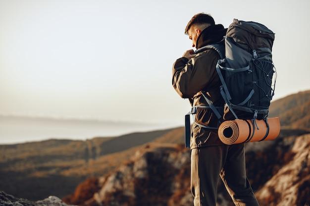 Viaggiatore giovane uomo caucasico con grande zaino escursionismo in montagna da solo