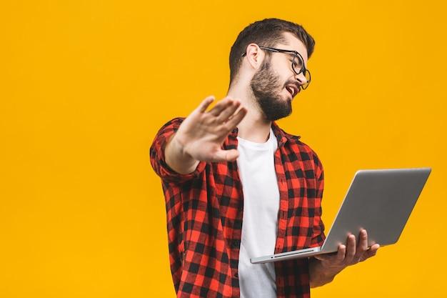 Giovane uomo caucasico che per mezzo del computer portatile del computer sopra isolato con la mano aperta che fa il fanale di arresto con l'espressione seria e sicura, gesto della difesa.