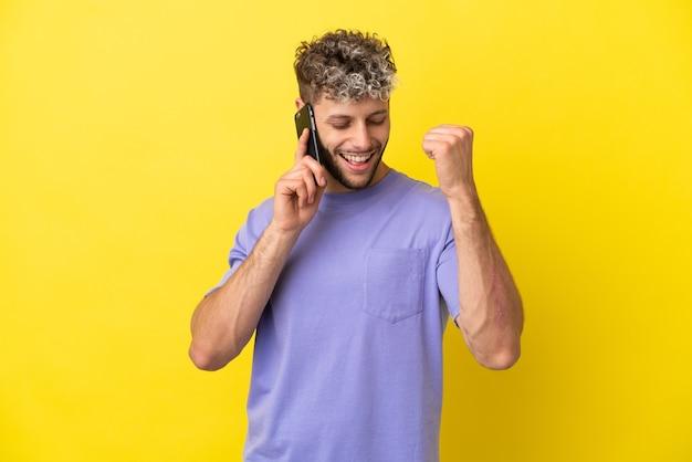 Giovane uomo caucasico che utilizza il telefono cellulare isolato su sfondo giallo che celebra una vittoria