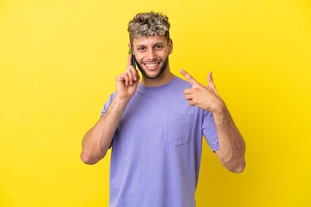 Giovane uomo caucasico che utilizza il telefono cellulare isolato su sfondo giallo dando un gesto di pollice in alto