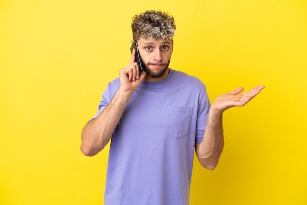 Giovane uomo caucasico che utilizza il telefono cellulare isolato su sfondo giallo avendo dubbi mentre alza le mani