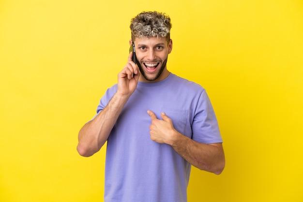Giovane uomo caucasico che utilizza il telefono cellulare isolato su sfondo giallo con espressione facciale a sorpresa