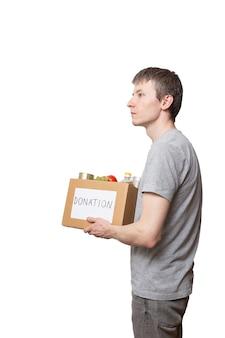 Volontario del giovane uomo caucasico che tiene il cibo della drogheria nella scatola di donazione del cartone