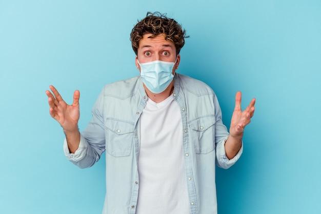 Giovane uomo caucasico che indossa una maschera antivirale sul blu che celebra una vittoria o un successo, è sorpreso e scioccato.