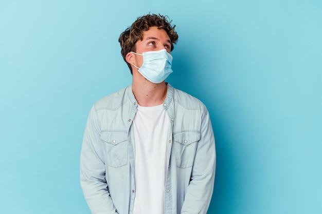 Giovane uomo caucasico che indossa una maschera antivirale sul blu che sogna di raggiungere obiettivi e scopi