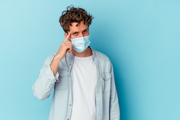 Giovane uomo caucasico che indossa una maschera antivirale isolata su sfondo blu che punta il tempio con il dito, pensando, concentrato su un compito.