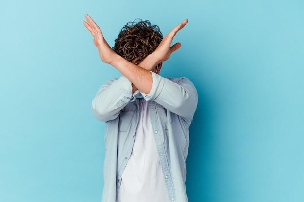 Giovane uomo caucasico che indossa una maschera antivirale isolata sulla parete blu mantenendo due braccia incrociate, concetto di negazione.