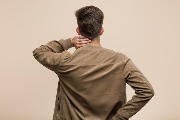 Giovane uomo caucasico che indossa una giacca marrone da dietro pensando a qualcosa.