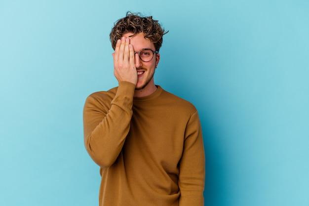 Giovane uomo caucasico che indossa occhiali da vista isolati sulla parete blu divertendosi che copre metà del viso con il palmo