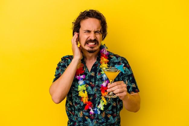 Giovane uomo caucasico che indossa una collana hawaiana tenendo un cocktail isolato su giallo che copre le orecchie con le mani.