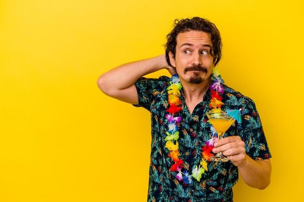 Giovane uomo caucasico che indossa una collana hawaiana che tiene un cocktail che tocca la parte posteriore della testa, pensando e facendo una scelta.