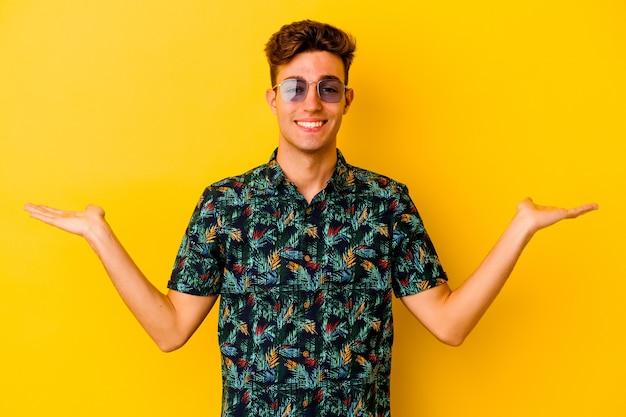 Il giovane uomo caucasico che indossa una camicia hawaiana isolata su sfondo giallo fa la scala con le braccia, si sente felice e fiducioso.