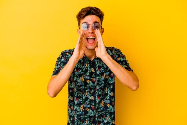Giovane uomo caucasico che indossa una camicia hawaiana isolata su sfondo giallo che grida eccitato davanti.