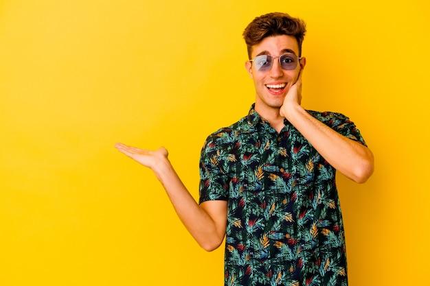 Il giovane uomo caucasico che indossa una camicia hawaiana isolata sulla parete gialla tiene lo spazio della copia su una palma, tiene la mano sulla guancia. stupito e deliziato.