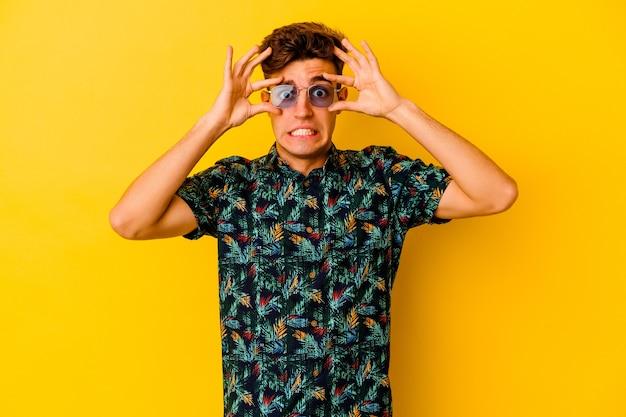 Giovane uomo caucasico che indossa una camicia hawaiana isolata sul muro giallo tenendo gli occhi aperti per trovare un'opportunità di successo