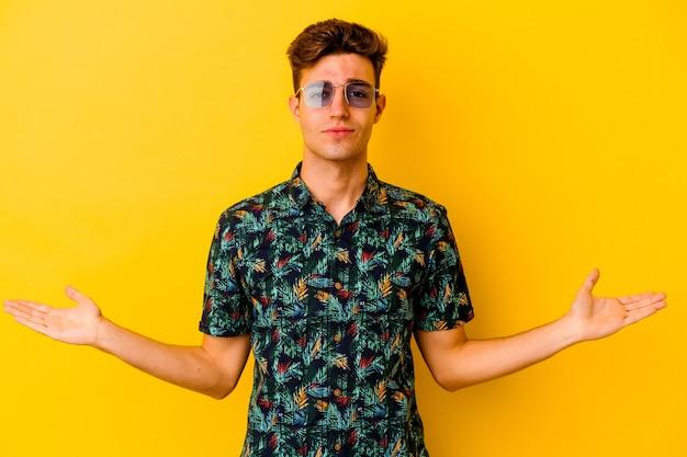 Giovane uomo caucasico che indossa una camicia hawaiana isolata sulla parete gialla che mostra un'espressione di benvenuto