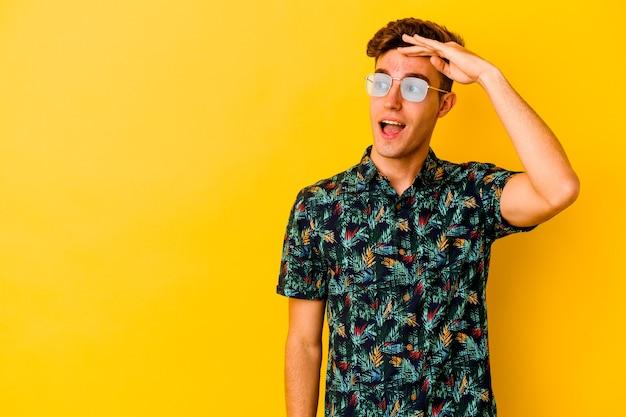 Giovane uomo caucasico che indossa una camicia hawaiana su giallo guardando lontano tenendo la mano sulla fronte.