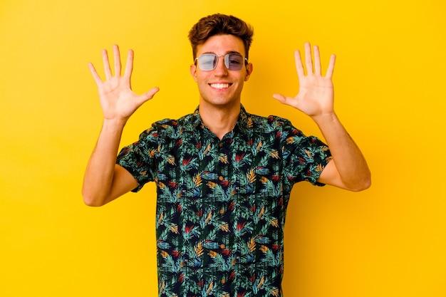 Giovane uomo caucasico che indossa una camicia hawaiana su giallo che mostra il numero dieci con le mani.