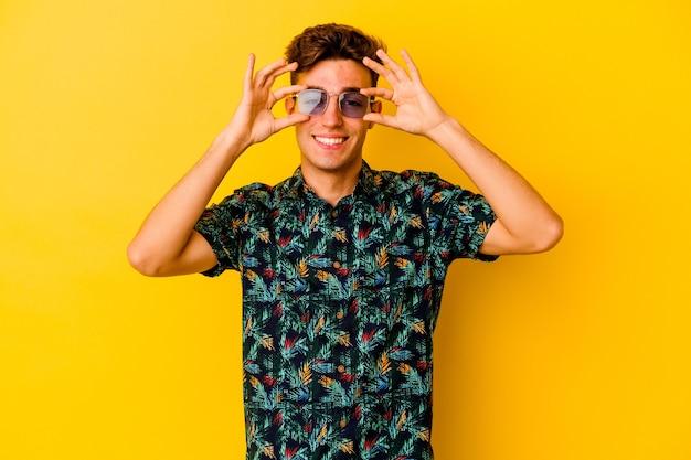 Giovane uomo caucasico che indossa una camicia hawaiana su giallo che mostra il segno giusto sugli occhi