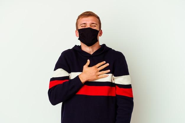 Il giovane uomo caucasico che indossa una maschera per virus isolato su sfondo bianco ride forte tenendo la mano sul petto.