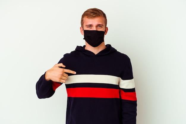 Giovane uomo caucasico che indossa una maschera per virus isolato su sfondo bianco persona che indica a mano uno spazio copia camicia, orgoglioso e fiducioso