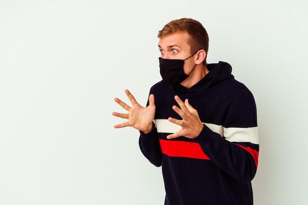 Il giovane uomo caucasico che indossa una maschera per virus isolato su sfondo bianco grida forte, tiene gli occhi aperti e le mani tese.
