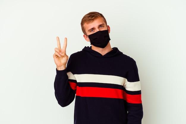 Giovane uomo caucasico che indossa una maschera per virus isolato su sfondo bianco che mostra il numero due con le dita.
