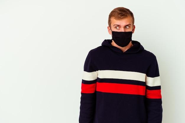 Giovane uomo caucasico che indossa una maschera per il virus isolato su bianco che è scioccato a causa di qualcosa