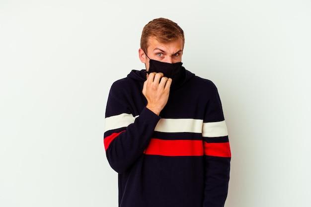 Giovane uomo caucasico che indossa una maschera per virus isolato su unghie mordaci bianche, nervose e molto ansiose.