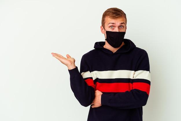 Il giovane uomo caucasico che indossa una maschera per virus isolato su bianco ha impressionato lo spazio della copia della tenuta sul palmo.