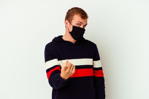 Giovane uomo caucasico che indossa una maschera per virus isolato su bianco che punta il dito contro di te come se invitando ad avvicinarsi.