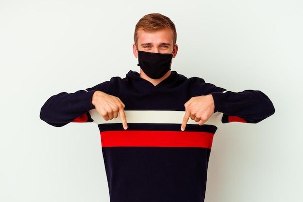 Giovane uomo caucasico che indossa una maschera per virus isolato su bianco punta verso il basso con le dita, sensazione positiva.