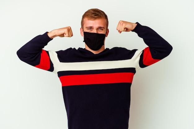 Giovane uomo caucasico che indossa una maschera per virus isolato su bianco che mostra il gesto di forza con le braccia