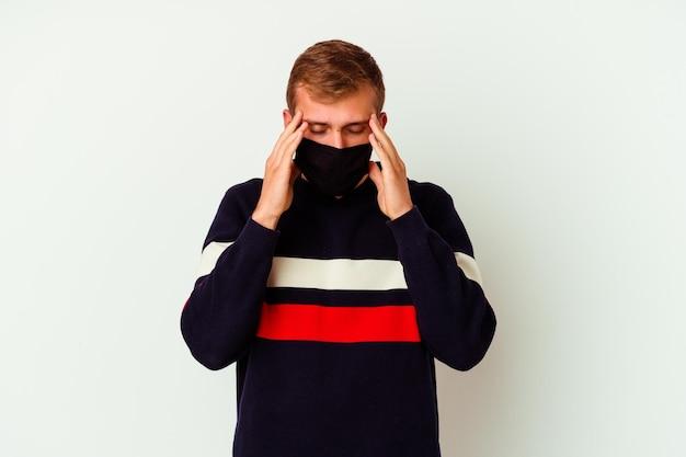 Giovane uomo caucasico che indossa una maschera per virus isolato su tempie commoventi bianche e avendo mal di testa.