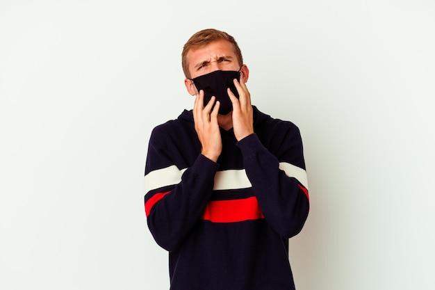 Giovane uomo caucasico che indossa una maschera per il virus isolato su bianco piagnucolando e piangendo sconsolato.