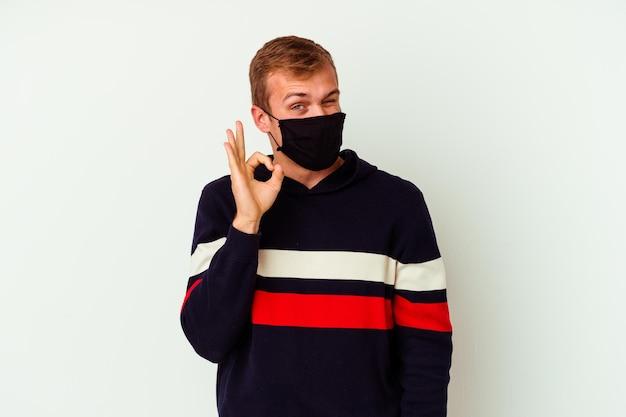 Il giovane uomo caucasico che indossa una maschera per il virus isolato su bianco strizza l'occhio e tiene un gesto giusto con la mano.