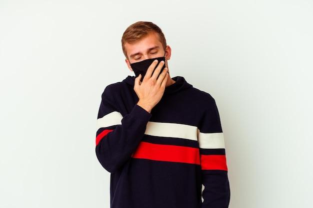 Giovane uomo caucasico che indossa una maschera per virus isolato su bianco che sbadiglia mostrando un gesto stanco che copre la bocca con la mano.