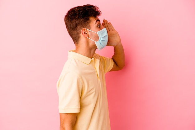Giovane uomo caucasico che indossa una protezione per il coronavirus isolato su sfondo rosa che grida e tiene il palmo vicino alla bocca aperta. Foto Premium