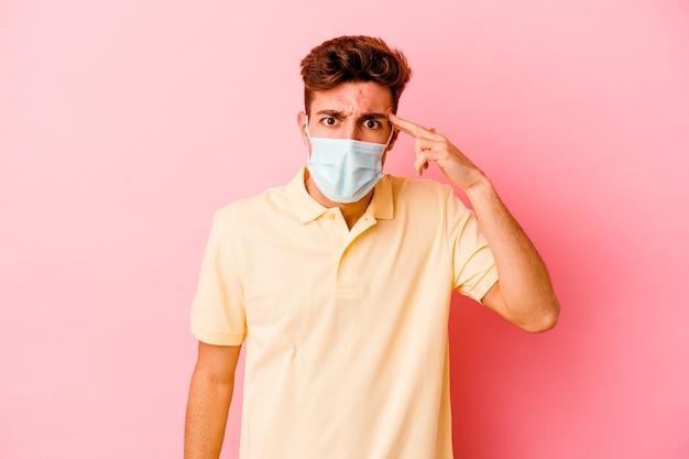 Giovane uomo caucasico che indossa una protezione per il coronavirus isolato su sfondo rosa che mostra un gesto di delusione con l'indice.