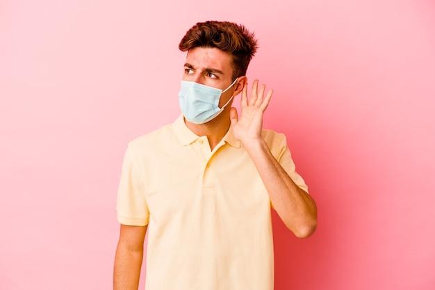 Giovane uomo caucasico che indossa una protezione per il coronavirus isolato sul muro rosa cercando di ascoltare un pettegolezzo.