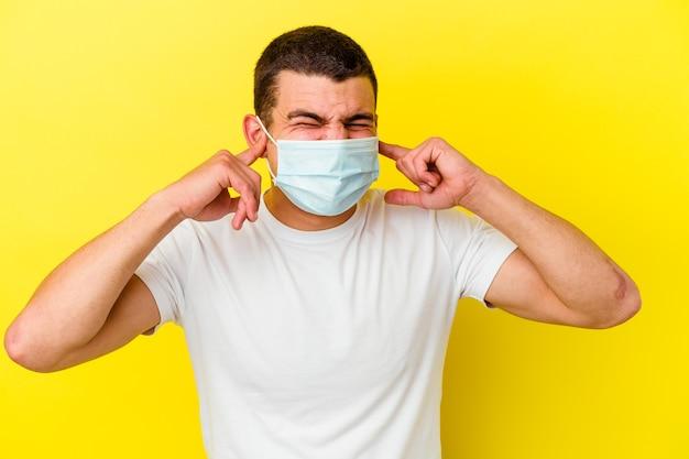Giovane uomo caucasico che indossa una protezione per il coronavirus isolato su sfondo giallo che copre le orecchie con le mani.