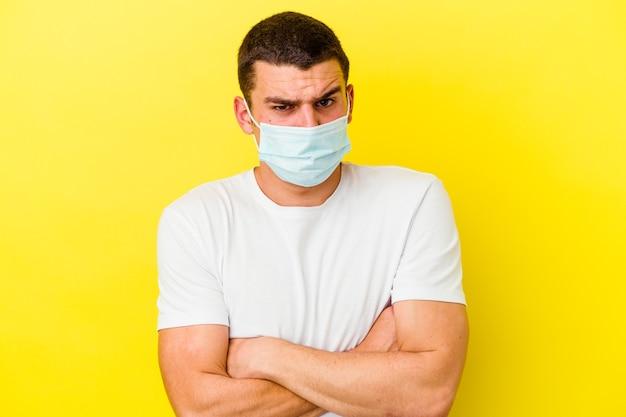 Il giovane uomo caucasico che indossa una protezione per il coronavirus isolato su sfondo giallo, il viso accigliato per il dispiacere, tiene le braccia conserte.